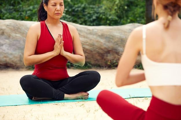 Zwei mädchen machen yoga und meditation im freien, paaren yoga-kurse, gesunden lebensstil, meditation und wellness.