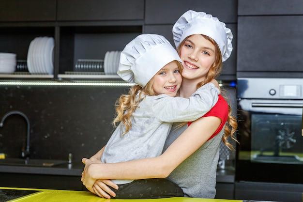 Zwei mädchen mit dem chefhut, der spaß in der küche umarmt und hat