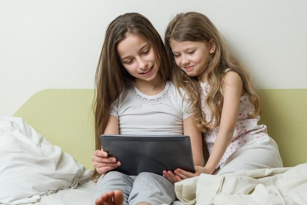 Zwei mädchen mit dem interesse, welches die tablette betrachtet und, plaudernd lacht