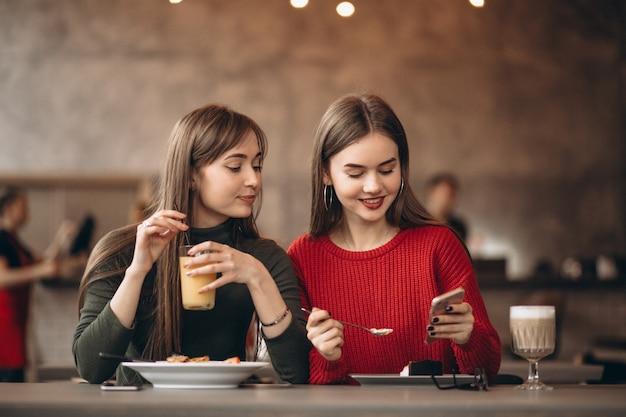 Zwei mädchen mit dem telefon, das in einem café sitzt