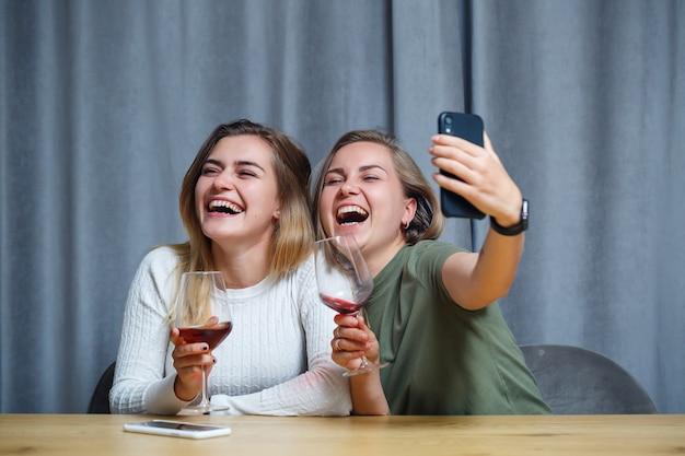 Zwei mädchen mit europäischem aussehen sitzen mit weingläsern an einem tisch und machen ein foto am telefon