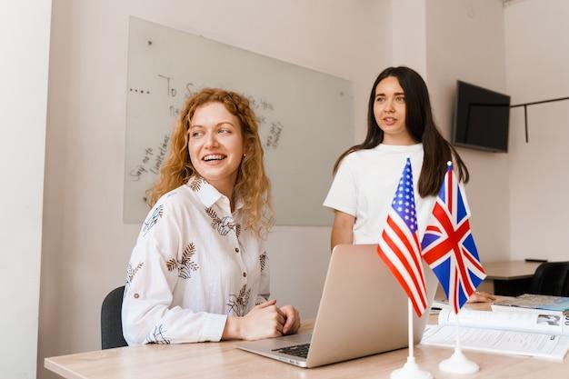 Zwei mädchen mit laptop betrachten fenster in der weißen klasse