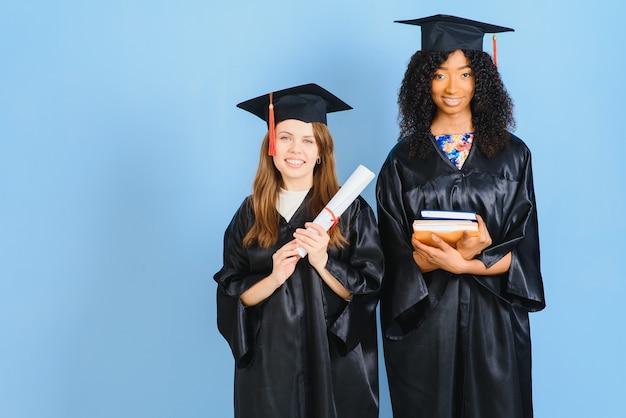 Zwei mädchen posieren für ein foto in schwarzen kleidern und besitzen ein diplom.