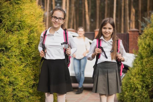 Zwei mädchen posieren mit schulranzen nach dem unterricht in der schule