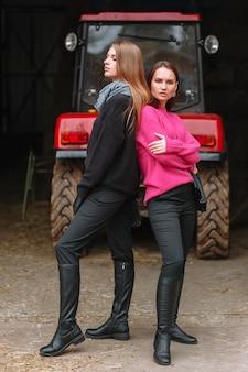 Zwei mädchen posieren neben einem traktor