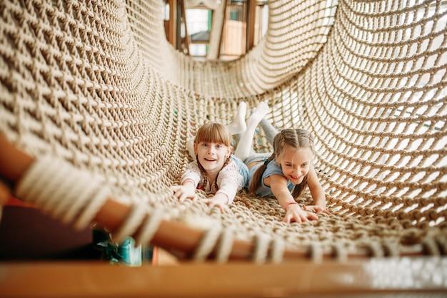 Zwei mädchen posiert im seilnetz, kinderspielzentrum