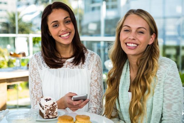 Zwei mädchen schauen zu, wie sie beim essen telefonieren