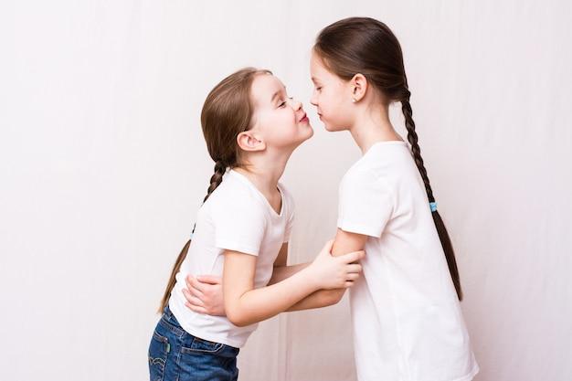 Zwei mädchen-schwestern küssen sich beim treffen