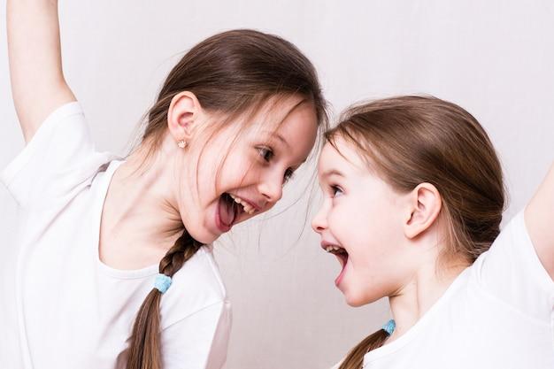Zwei mädchen schwestern lächeln einander emotional an