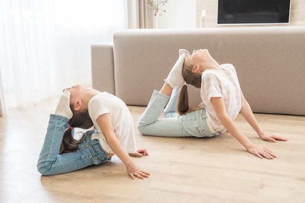 Zwei mädchen schwestern praktizieren yoga zu hause und strecken sich in king cobra pose