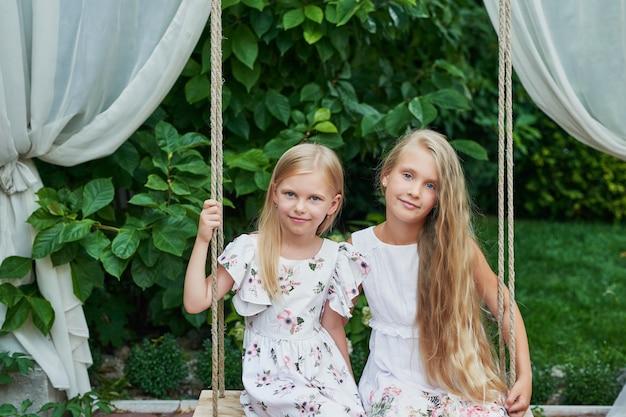 Zwei mädchen schwestern reiten auf einer schaukel im sommer im garten