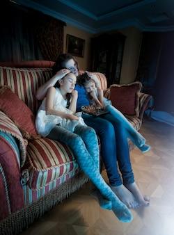 Zwei mädchen sind nachts beim fernsehen mit ihrer mutter eingeschlafen