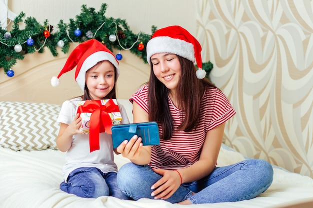 Zwei mädchen sitzen auf dem bett in weihnachtsmützen mit geschenkbox und kommunizieren per videolink im smartphone