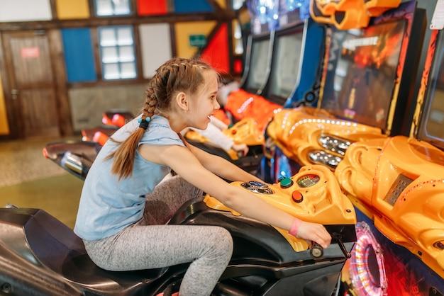 Zwei mädchen spielen spielautomat, unterhaltungszentrum