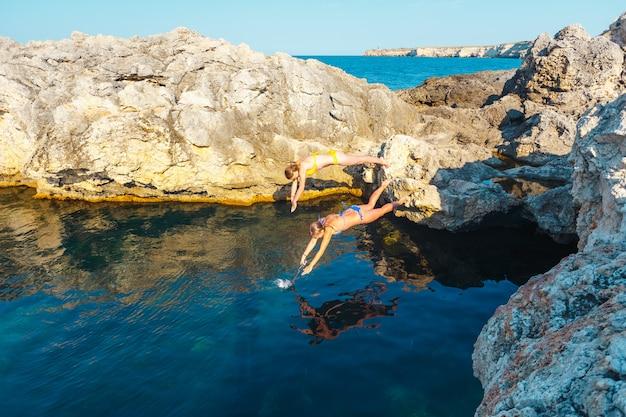 Zwei mädchen springen von einer klippe ins meerwasser