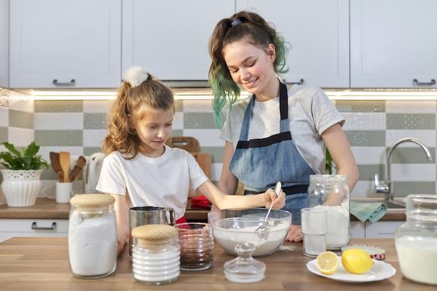Zwei mädchen, teenager und jüngere schwester bereiten gemeinsam kekse in der küche zu. kinder mehl in schüssel mischen, zutaten hinzufügen. familie, freundschaft, spaß, gesundes hausgemachtes essen