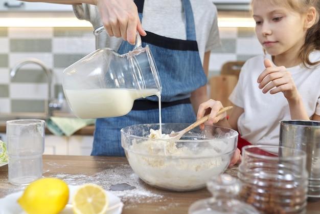 Zwei mädchen, teenager und jüngere schwester bereiten gemeinsam kekse in der küche zu. kinder mischen das mehl in einer schüssel, gießen milch in den teig. familie, freundschaft, spaß, gesundes hausgemachtes essen