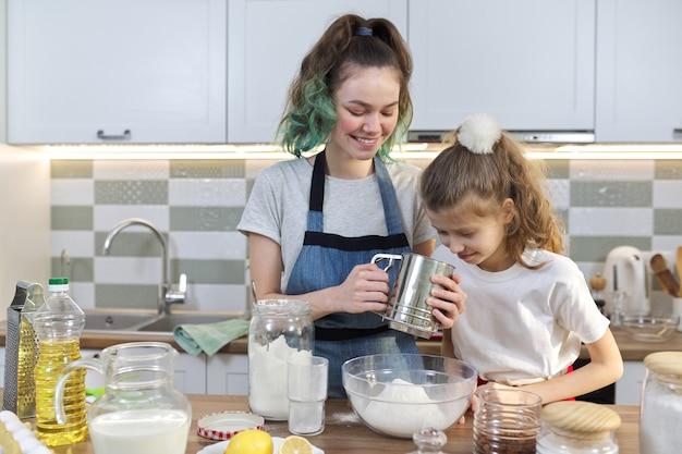 Zwei mädchen, teenager und jüngere schwester bereiten gemeinsam kekse in der küche zu. kinder rühren mehl, der älteste zeigt den jüngsten. familie, freundschaft, spaß, gesundes hausgemachtes essen
