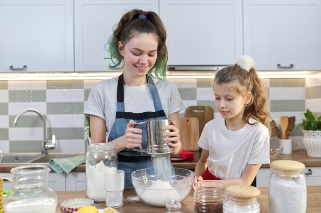 Zwei mädchen, teenager und jüngere schwester, die gemeinsam kekse in der küche zubereiten. kinder rühren mehl, der älteste zeigt den jüngsten. familie, freundschaft, spaß, gesundes hausgemachtes essen