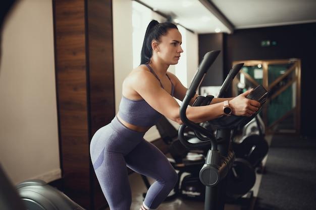 Zwei mädchen trainieren im fitnessstudio. ein mädchen unterrichtet eine freundin und hilft ihr beim training.
