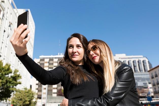 Zwei mädchen umarmen sich und machen ein selfie in der stadt.