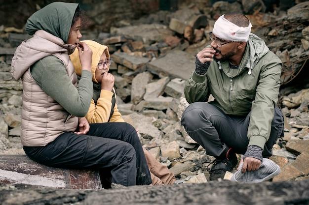 Zwei mädchen und ein junger mann essen zusammen in trümmern