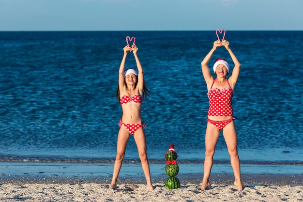 Zwei mädchen und ein schneemann aus wassermelonen in weihnachtsmützen mit weihnachtszuckerstangen