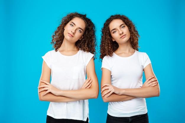 Zwei mädchen zwillinge posieren mit verschränkten armen über der blauen wand