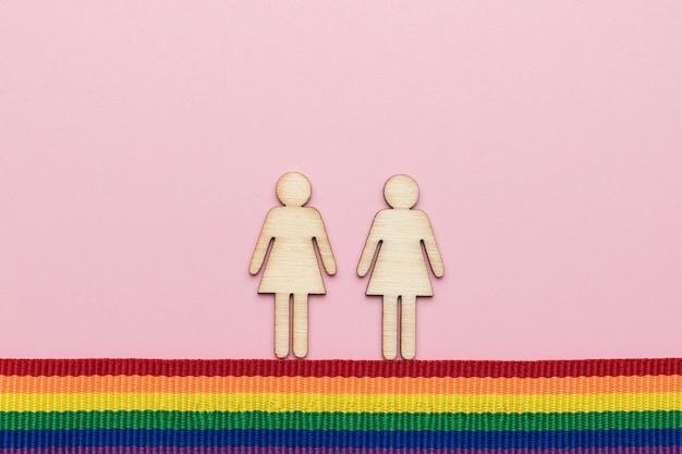 Zwei mädchenfiguren auf einem band in lgbt-farben. flach liegen.