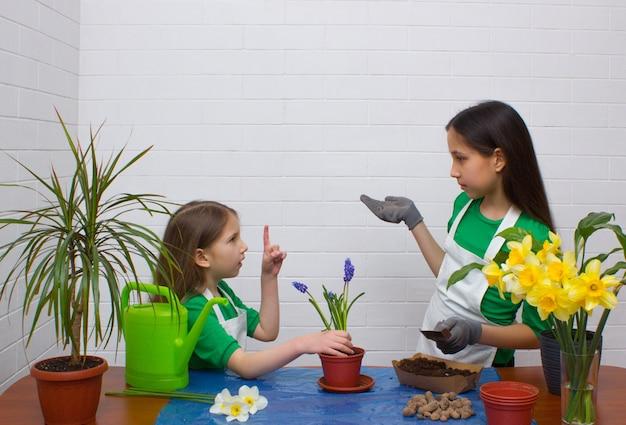 Zwei mädchenschwestern verpflanzen blumen, das jüngste mädchen zeigt mit dem zeigefinger nach oben, um eine idee zu haben