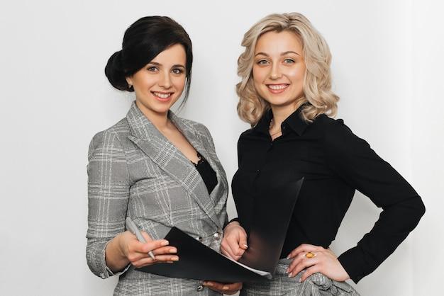 Zwei mädchensekretäre lächeln auf einem grauen hintergrund