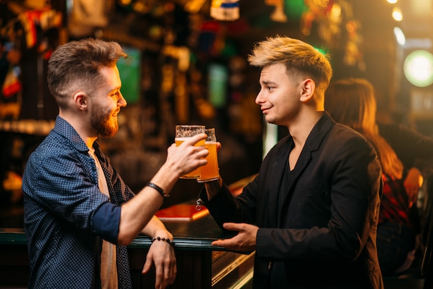Zwei männer an der theke hoben ihre gläser mit bier für den sieg im spiel in einer sportkneipe, eine glückliche freizeit der fußballfans