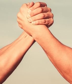 Zwei männer beim armdrücken. armdrücken. nahaufnahme. freundlicher händedruck, freunde grüßen, teamwork, freundschaft. händedruck, arme