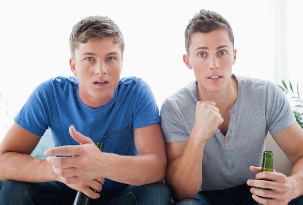 Zwei männer beobachten etwas, während sie geschockt aussehen