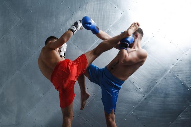 Zwei männer boxer kämpfen gegen muay thai kickboxen hgh kick stahl hintergrund.