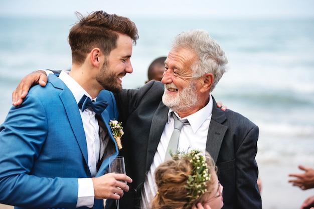 Zwei männer, die am strand eine strandhochzeit umarmen