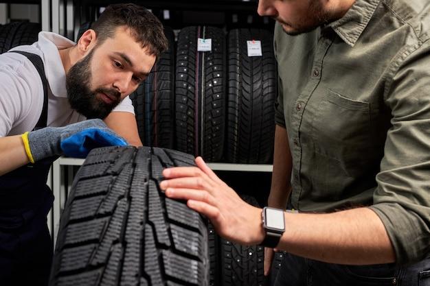Zwei männer, die die oberfläche von autoreifen betrachten und über die vorteile von winterreifen für automobile diskutieren, sprechen, berühren und untersuchen