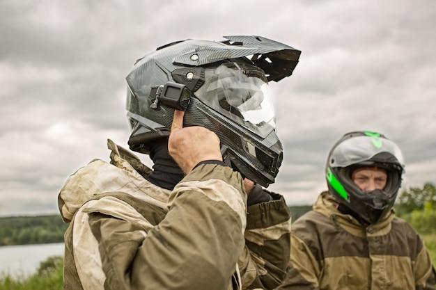 Zwei männer, die draußen motorradsturzhelme und -uniformen tragen.