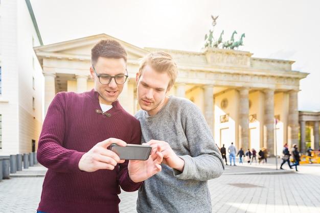 Zwei männer, die einen smartphone in berlin betrachten