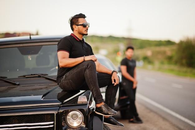 Zwei männer, die ganz schwarz posieren, posieren in der nähe von geländewagen