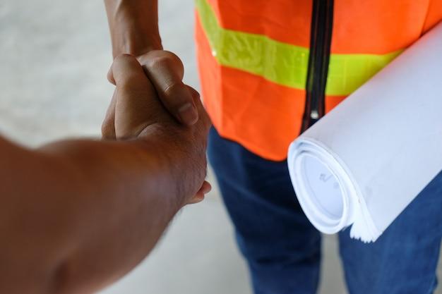Zwei männer, die hand rütteln, nachdem eine vereinbarung beendet worden ist oder nah oben arbeiten