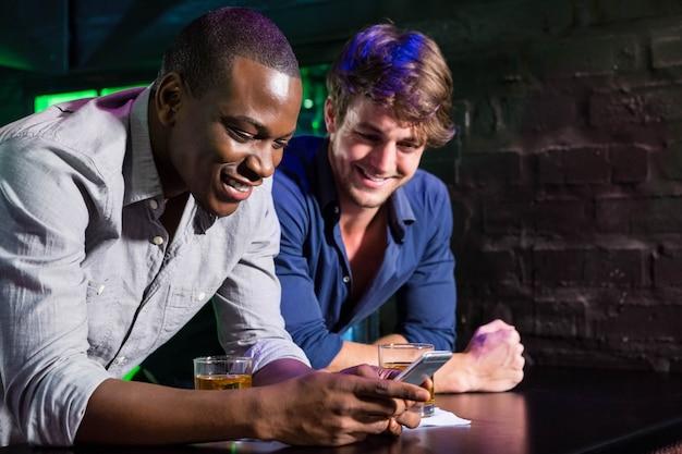 Zwei männer, die handy betrachten und beim trinken des whiskys am stangenzähler in der stange lächeln