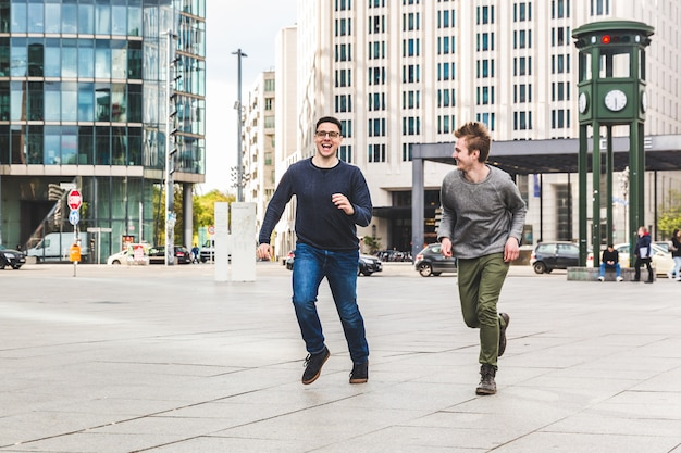 Zwei männer, die in die stadt spielen und laufen