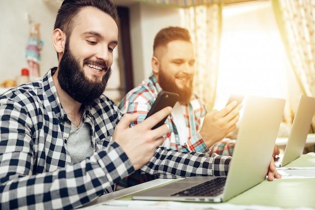 Zwei männer, die in einem café sitzen, betrachten handys