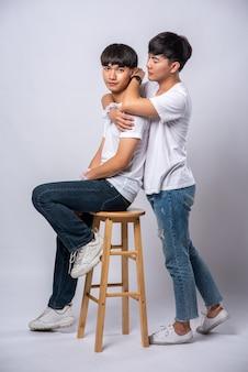 Zwei männer, die sich lieben, umarmen sich und setzen sich auf einen stuhl.