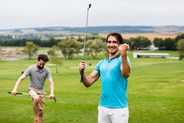 Zwei männer, die spaß auf golfplatz haben