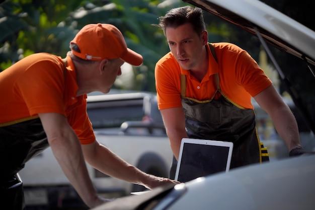 Zwei männer, ein mechaniker, kontrollieren und konditionieren ihre motoren mit einem laptop.
