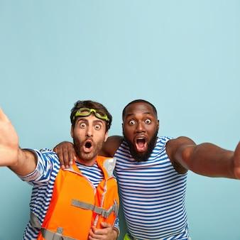 Zwei männer gemischter rassen starren mit geschocktem gesichtsausdruck, machen ein selfie-porträt, umarmen sich, lassen die kiefer fallen und verbringen ihre freizeit am meer