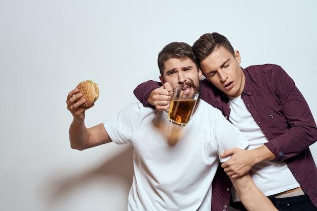 Zwei männer haben spaß, trinken bier und essen fast food.
