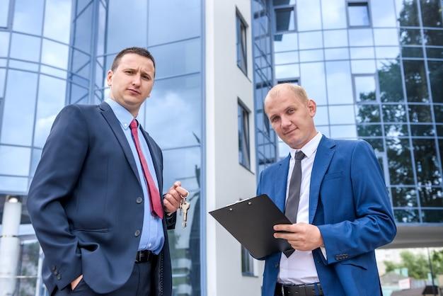 Zwei männer in anzügen mit zwischenablage und schlüsseln verhandeln